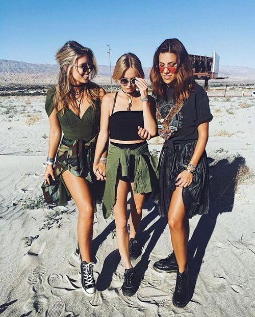 Três mulheres em festival estilo Lollapalooza com jaquetas amarradas na cintura