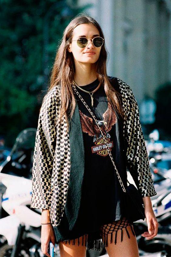 Mulher com camiseta de banda e bolsa à tira colo em festival estilo Lollapalooza