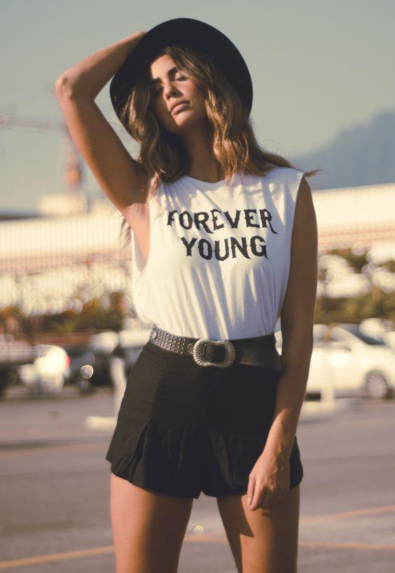 Mulher em festival estilo Lollapalooza com camiseta escrito Forever Young