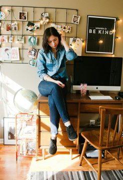 Mulher sentada em mesa de home office com look jeans