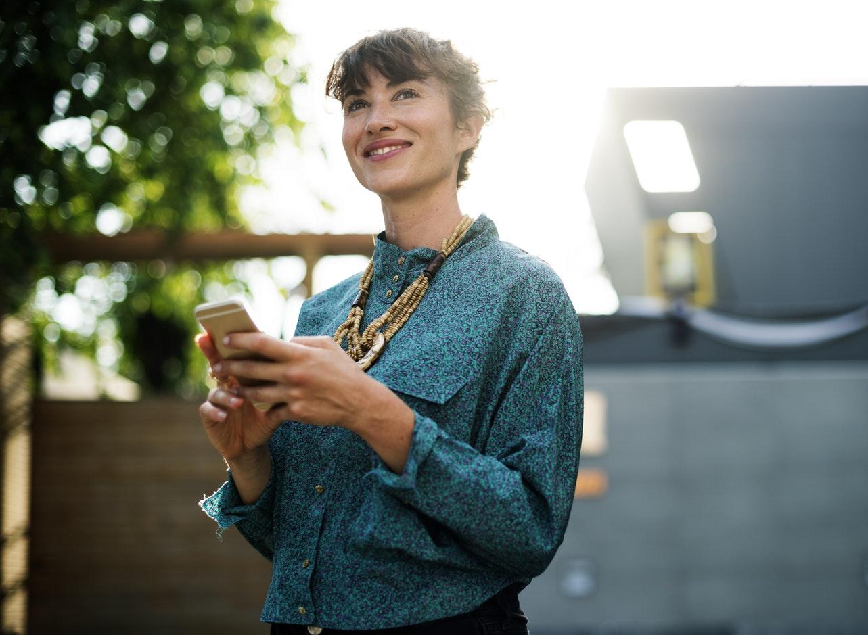 Mulher sorrindo com celular nas mãos compras no Instagram