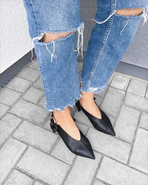 Close de pernas femininas com scarpin decote V preto e calça jeans rasgada