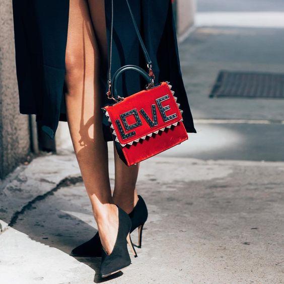 Close de pernas femininas com scarpin decote V preto de salto alto