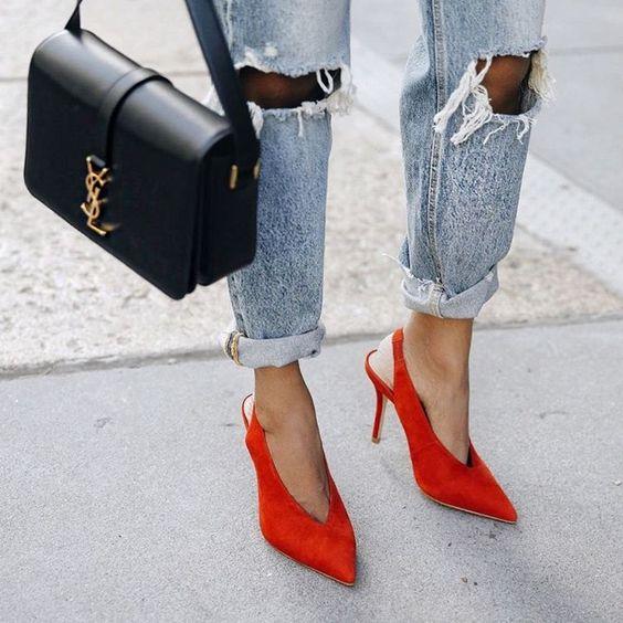 Close de pernas femininas com scarpin decote V e calça jeans rasgada