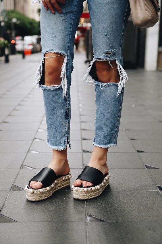 Close de pés femininos usando sapato flatform e calça jeans rasgada