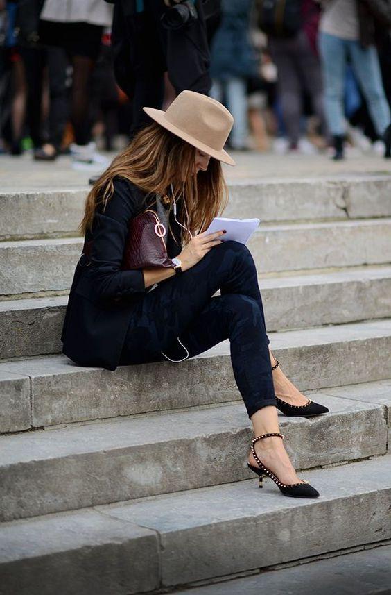 Mulher sentada em escada com look preto e sapatos kitten heels