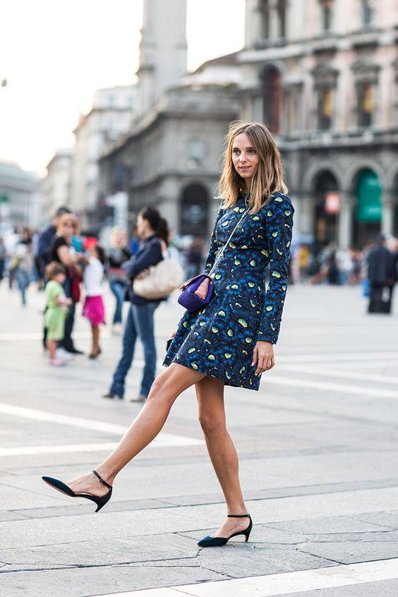 Mulher com vestido estampado levantando a perna com sapatos kitten heels