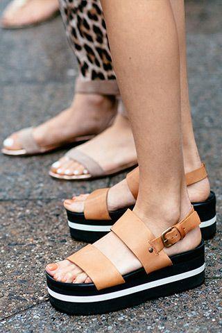 Close de dois pares de pés femininos usando flatforms