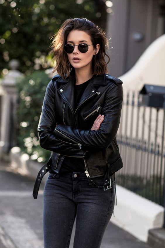 Mulher com Ray-Ban, jaqueta preta e calça preta