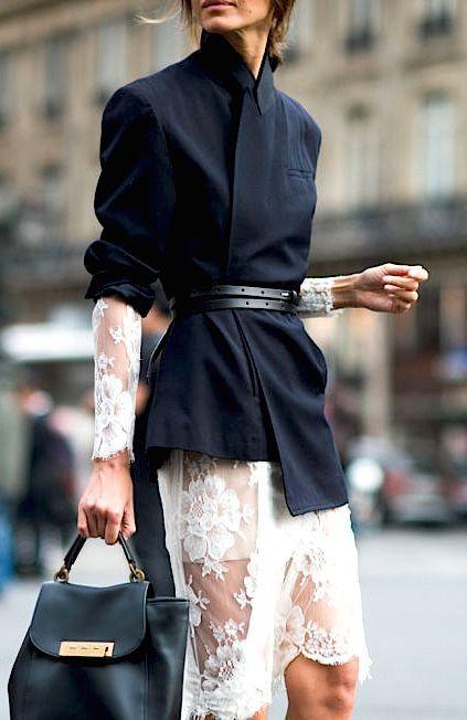 Mulher com cinto fino por cima de vestido e casaco