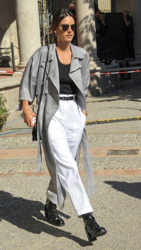 Mulher com calça branca, casaco cinza e cinto fino
