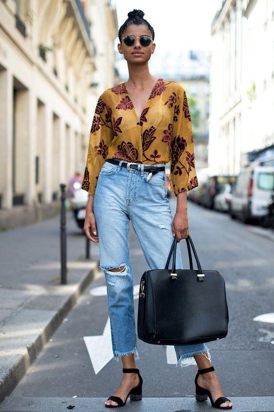 Mulher com camisa estampada e calça jeans com cinto fino