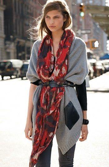 Mulher com cinto fino por cima de lenço e casaco