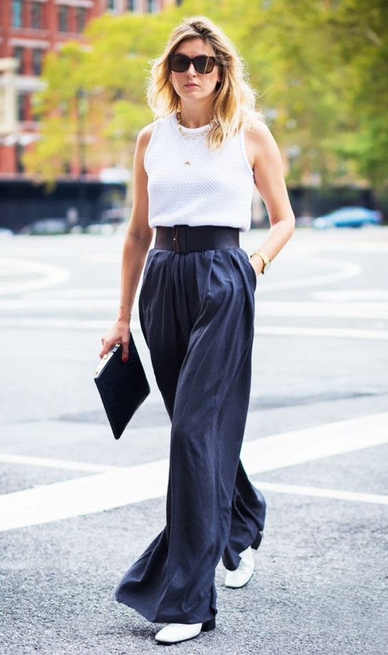 Mulher usando regata branca e calça com cinto largo