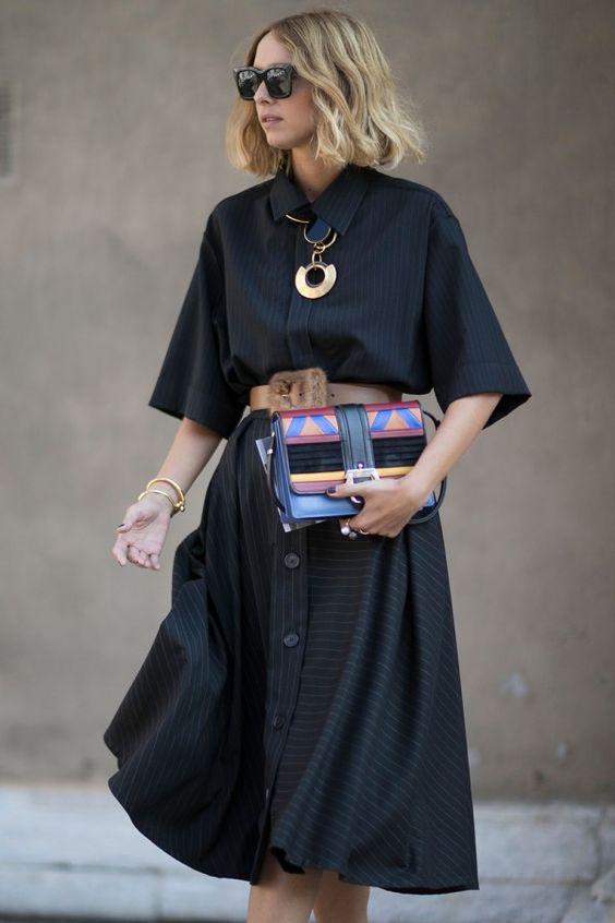Mulher de vestido preto com cinto largo carregando bolsa colorida