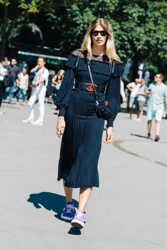 Mulher com vestido preto e cinto largo marcando cintura