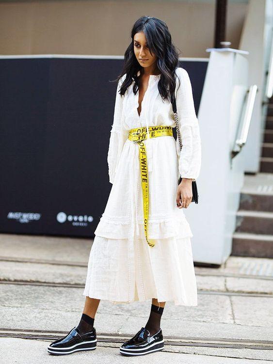 Mulher com vestido branco e cinto amarelo longo