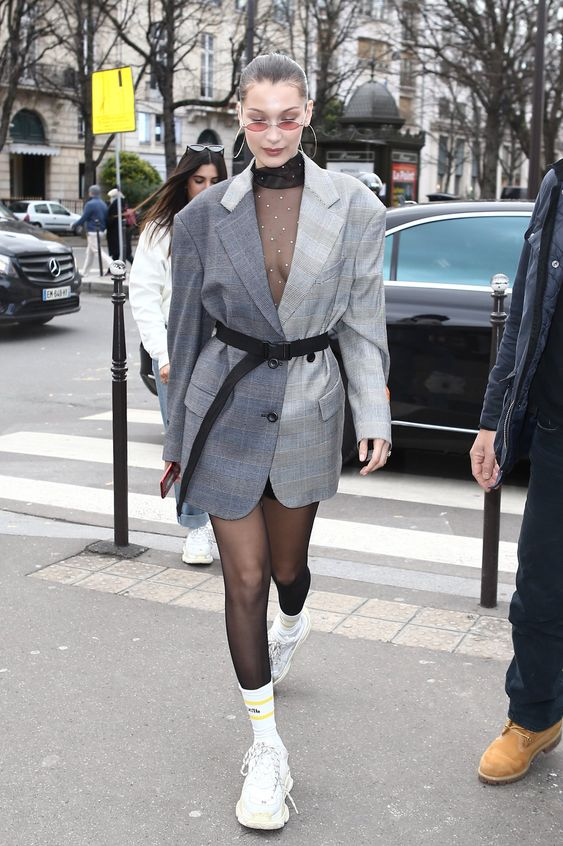 Mulher com blazer e meia calça com cinto longo por cima