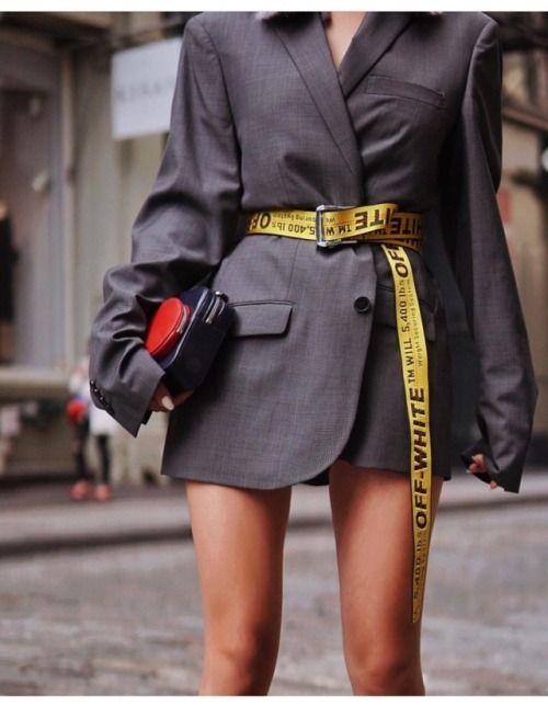 Mulher de blazer e cinto amarelo longo