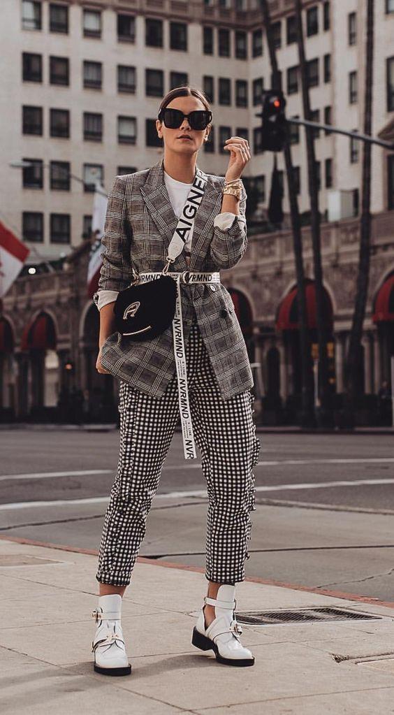 Mulher com look xadrez e cinto longo