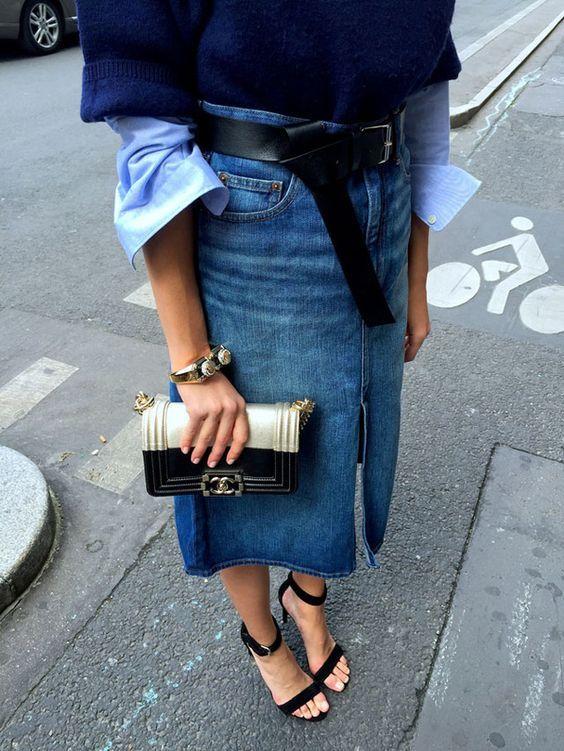 Mulher usando saia jeans comprida e cinto preto longo