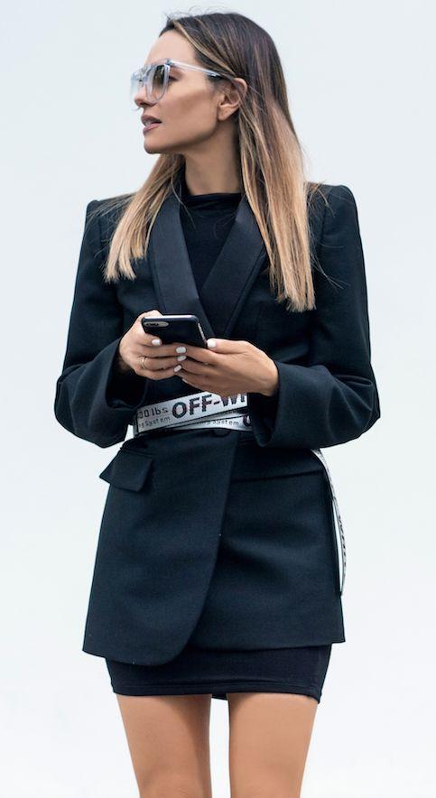 Mulher com cinto por cima do blazer com saia