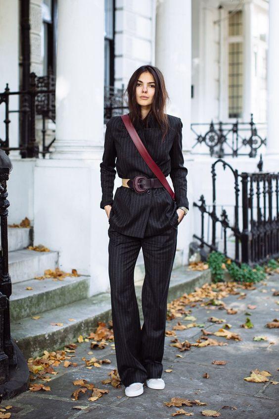 Mulher com cinto por cima do blazer com look risca de giz