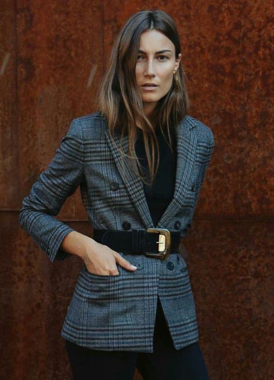 Mulher com cinto por cima do blazer xadrez
